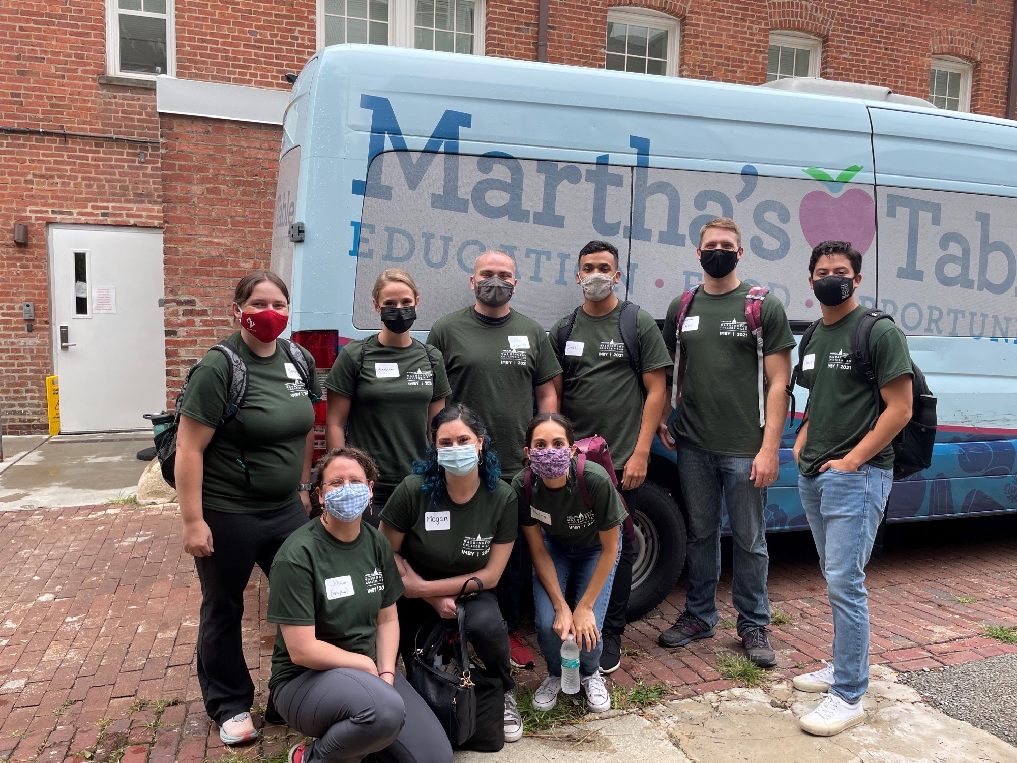Students volunteer at Martha's Table, stand by van with logo.