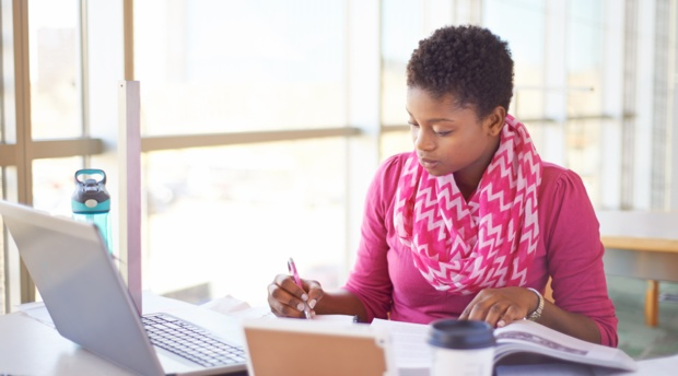 Woman studying with laptop and papers.